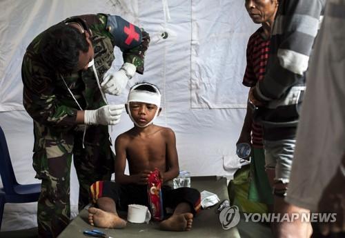 2018년 8월 5일 규모 7.0의 강진으로 대규모 인명피해가 발생한 이네시아 롬복섬에서 8일 군의관이 다친 소년을 치료하고 있다/사진=연합뉴스