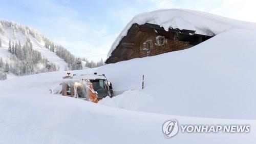 오스트리아 잘츠부르크 인근 마을에 내린 눈이 집 지붕까지 쌓인 가운데 제설차가 11일(현지시간) 집 앞으로 길을 내고 있다./ 사진=연합뉴스