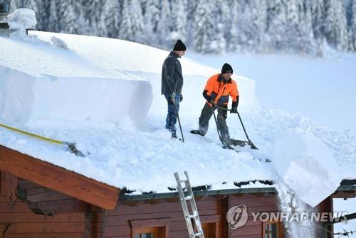 오스트리아 운터타우어른에서 11일(현지시간) 두 사람이 지붕 위의 눈을 치우고 있다./ 사진=연합뉴스