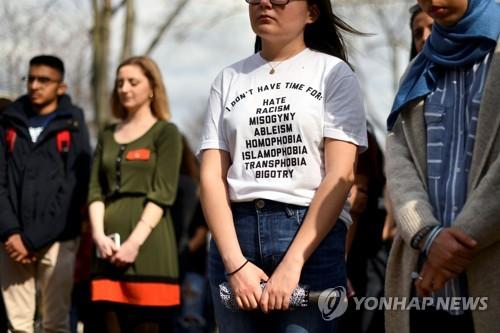 미국 필라델피아주 펜실베이니아 대학교에서 15일(현지시간) 뉴질랜드 총기난사 사건의 희생자를 추모하는 집회가 열린 가운데, 한 여성 참가자가 인종차별, 여성혐오, 동성애자 혐오 ...