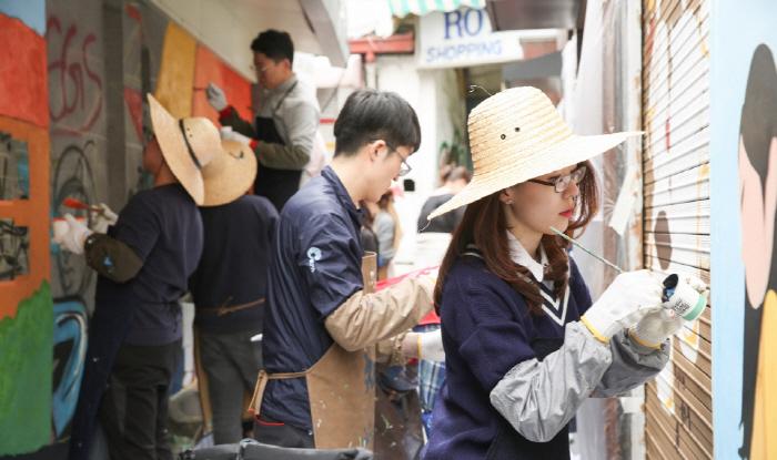 현대산업개발 직원들이 지난 20일 이태원동 골목길에 벽화를 그리고 있다. [사진 = 현대산업개발]<br />
