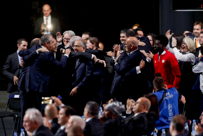 Delegates of Canada, Mexico and the United States celebrate after winning a joint bid to host the 20...