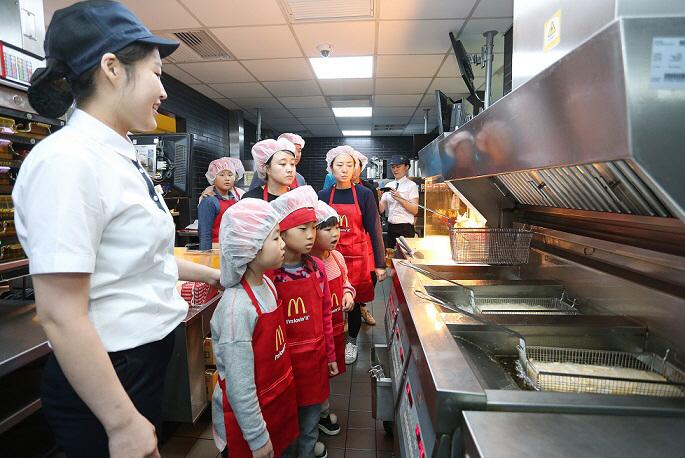 맥도날드 송파잠실DT점에서 열린 주방 공개의 날 행사에서 참가 고객들이 후렌치 후라이 조리 과정을 보고 있다. [사진제공 = 맥도날드]