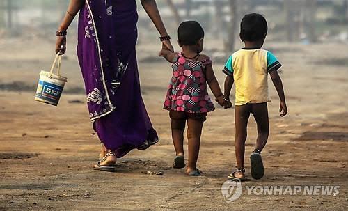 인도의 한 여성이 야외에 설치된 화장실로 자녀들을 데려가는 모습. 전 세계 인구 중 45억 명이 안전한 화장실이 없는 환경에서 살고 있다. [사진 출처 = 연합뉴스]