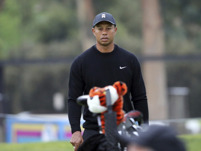 Tiger Woods walks the third green during the pro-am round at the Genesis Open golf tournament at Riv...