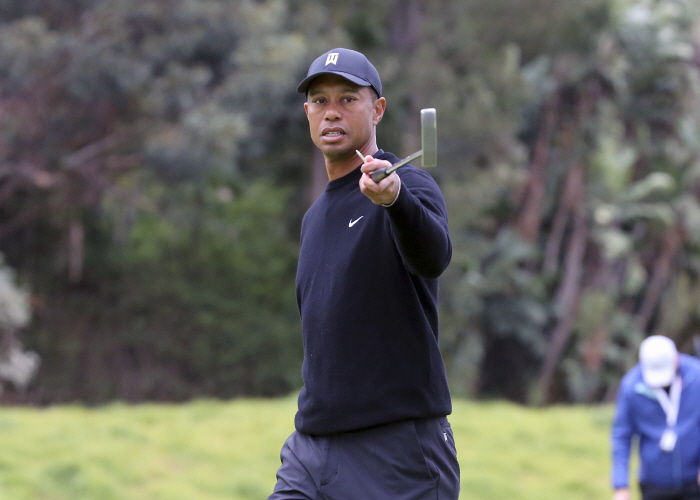 Tiger Woods warns spectators that someone is hitting behind them during the Pro-Am round of the Gene...