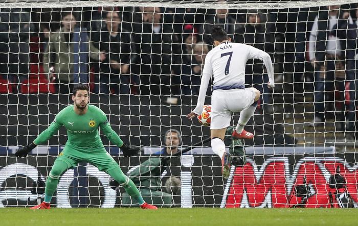 Tottenham midfielder Heung-Min Son, right, scores the opening goal against Dortmund goalkeeper Roman...