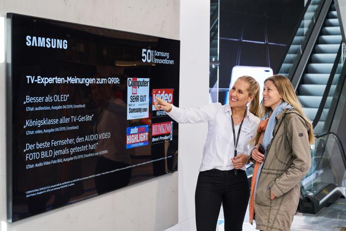 독일 프랑크푸르트 시내에 위치한 삼성 쇼케이스 매장에서 판매 직원이 고객에게 영상·음향기기 전문 매체들로부터 호평받은 QLED TV를 소개하고 있다. [사진제공 = 삼성전자]