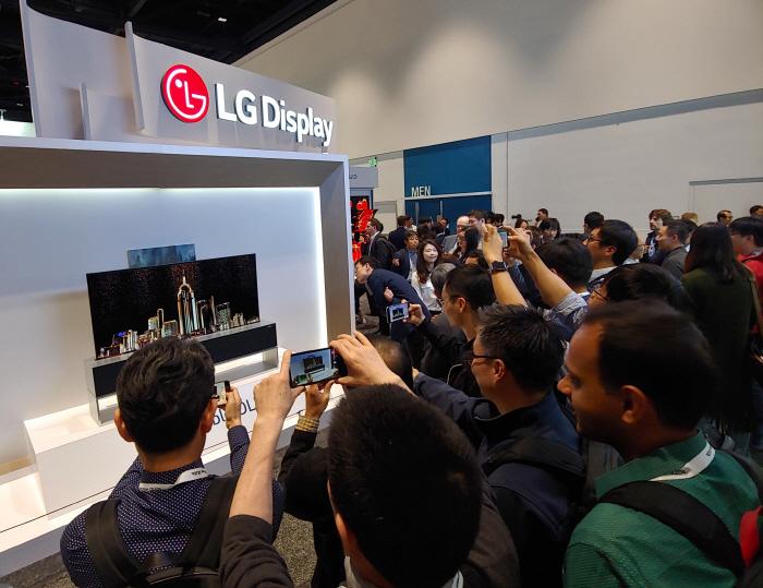 16일(현지시간) 미국 새너제이에서 열린 SID 2019에서 관람객들이 LG디스플레이 부스 앞에 전시된 65인치 롤러블 OLED TV를 보고 있다. [사진제공 = LG디스플레이]