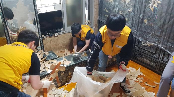 화성자원봉사단원들이 6.25 참전 유공자 집을 방문해 보수공사를 진행하고 있다. [사진 제공 = 화성산업]