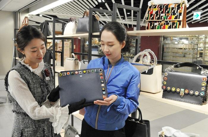 롯데백화점 고객이 해외 명품 할인 상품을 고르고 있다.